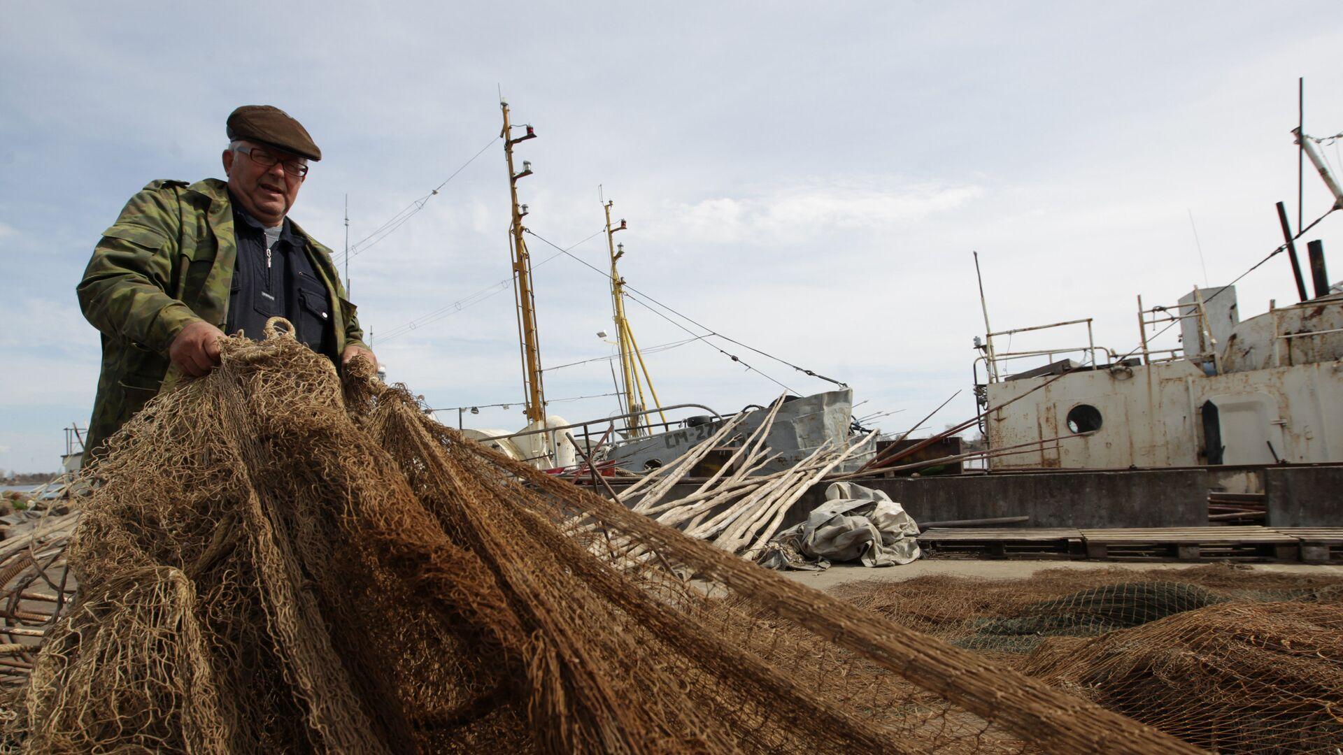 Рыбак проверяет сеть перед выходом на сезонный лов - РИА Новости, 1920, 18.10.2020