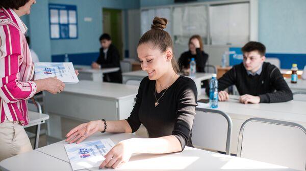 Преподаватель раздает пакеты с экзаменационными заданиями перед началом единого государственного экзамена по географии