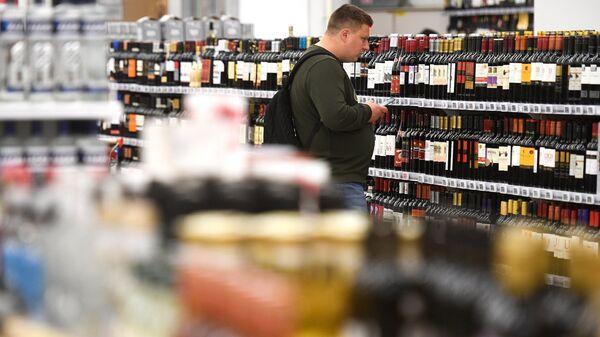 Покупатель в отделе алкогольной продукции гипермаркета Ашан