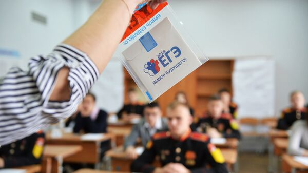 Преподаватель демонстрирует пакет и компакт-диск с заданиями перед началом ЕГЭ по математике. Архивное фото