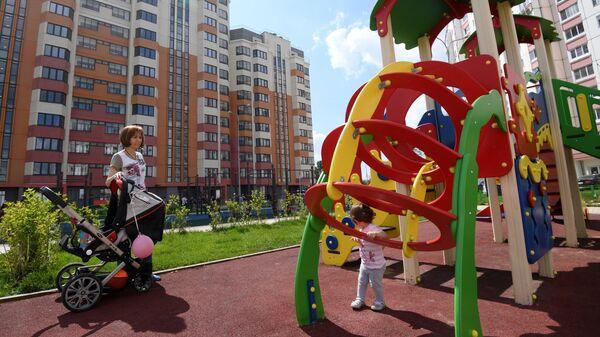 Детская площадка у многоэтажного жилого дома, предназначенного для переселения участников программы реновации
