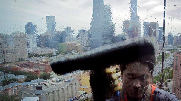 Работник моет окно офисного здания в деловом районе Пекина