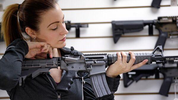 Девушка с автоматической винтовкой в магазине по продаже оружия в США