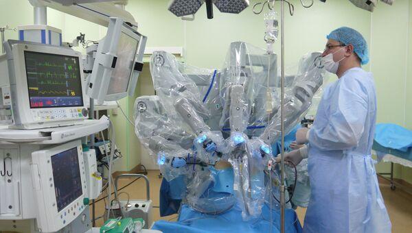 Робот-хирург приступает к операции. Ассистент профессора Михаила Еникеева, стоящий у операционного стола, следит за состоянием пациента