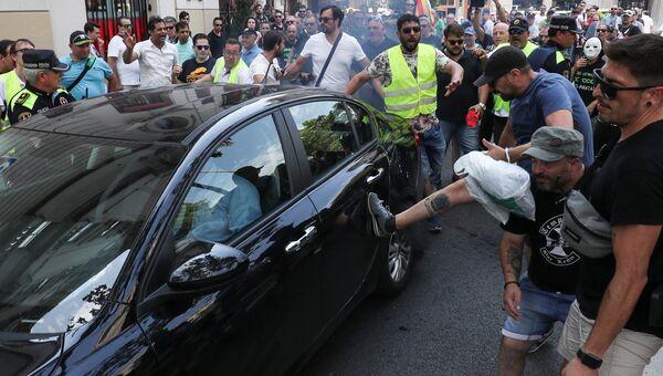 Участник забастовки таксистов в Барселоне пинает автомобиль, работающий с сервисом Uber. 25 июля 2018