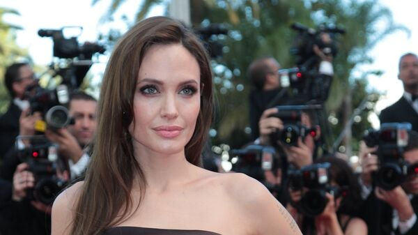 Актриса Анжелина Джоли позирует на Красной дорожке перед конкурсным показом фильма The Tree Of Life в рамках 64-го Ежегодного Каннского кинофестиваля