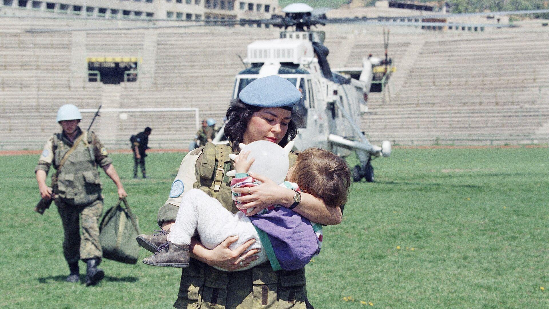 Женщина-солдат ООН несет двухлетнюю девочку, которую эвакуировали из города Горажде в Сараево, 25 апреля 1994 года - РИА Новости, 1920, 22.01.2020