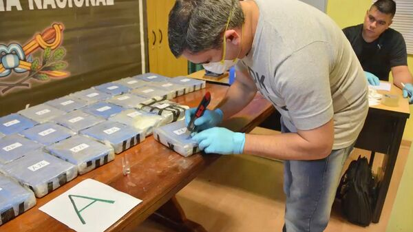 Аргентинские полицейские вскрывают пакеты с кокаином, предназначавшимся для контрабанды в Россию. Архивное фото