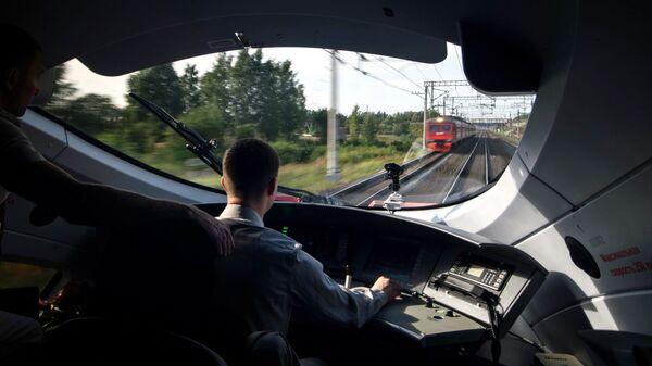 Машинист в кабине высокоскоростного поезда