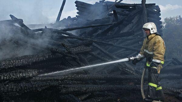 Сотрудник противопожарной службы у сгоревшего здания церкви Успения Божией Матери в Кондопоге в Карелии. 10 августа 2018