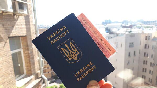 Гражданин Украины держит паспорт и патент на работу в РФ