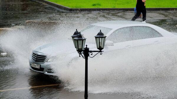 Автомобиль едет по улице Москвы во время дождя