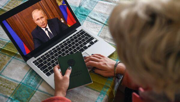 Жительница Новосибирска смотрит трансляцию обращения президента РФ Владимира Путина к гражданам России