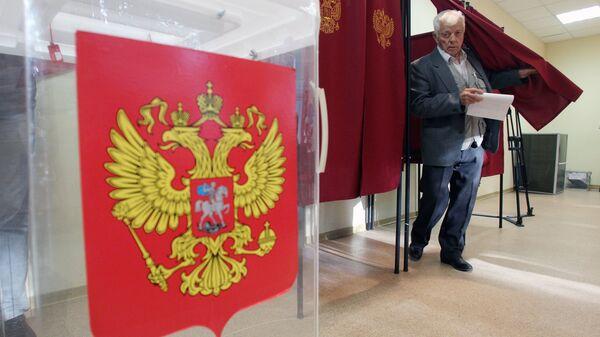 Избиратель голосует на избирательном участке. Архивное фото