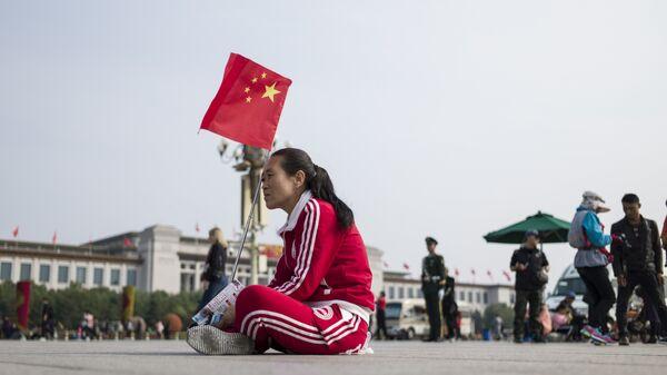 Женщина с флагом Китая на площади в Пекине. Архивное фото