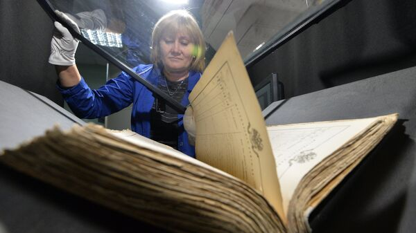 Сотрудница сканирует архивные документы