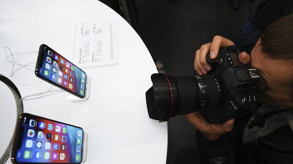 Фоторепортер фотографирует телефоны iPhone XS и iPhone XS Max в магазине re:Store на Тверской улице в Москве