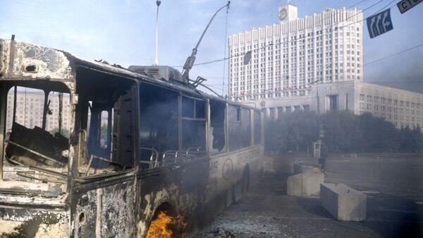 Обгорелый троллейбус у здания Дома Советов Российской Федерации во время интенсивного танкового обстрела. Архивное фото