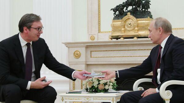 Президент Сербии Александр Вучич вручает президенту РФ Владимиру Путину книгу Моя прекрасная Сербия во время встречи в Москве. 2 октября 2018