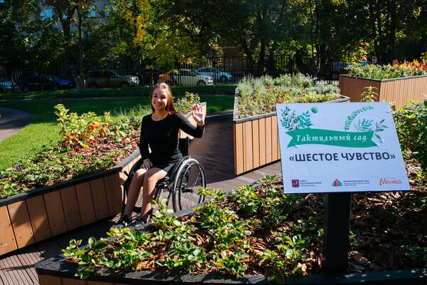 Девушка на инвалидной коляске в тактильном парке