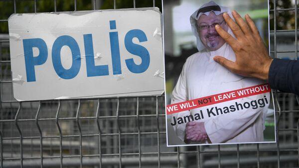 Участник акции протеста с портретом саудовского журналиста Джамаля Хашукджи у здания консульства Саудовской Аравии в Стамбуле, Турция