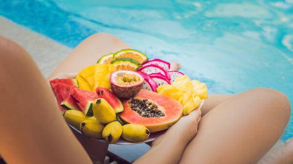 Девушка с фруктами отдыхает у бассейна
