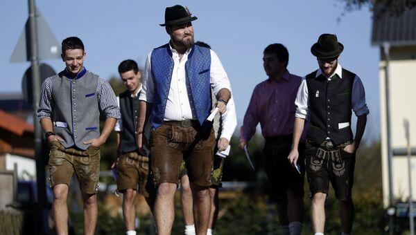 Мужчины в традиционной баварской одежде идут к избирательному участку в городе Майзах, Германия