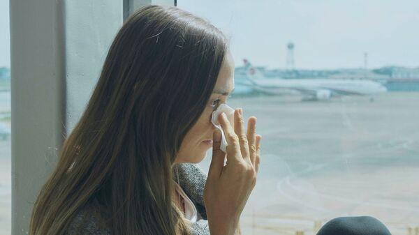 Девушка плачет в аэропорту