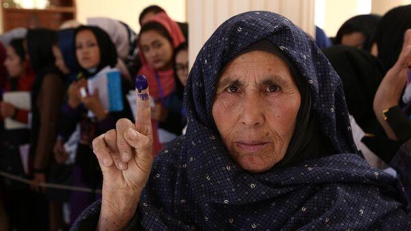 Женщина после голосования на одном из избирательных участков в Кабуле