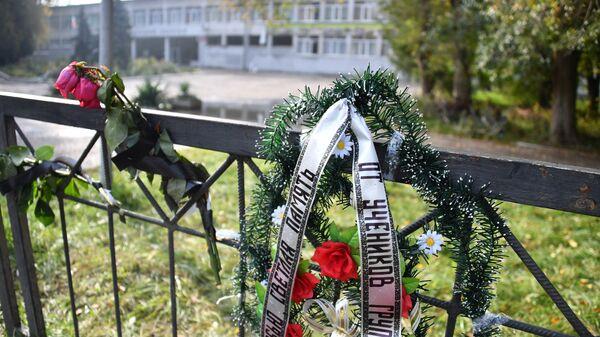 Траурный венок и цветы на ограде недалеко от Керченского политехнического колледжа