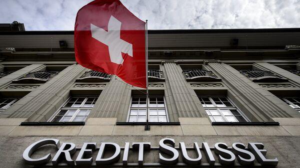 Флаг Швейцарии над вывеской банка Credit Suisse в Берне