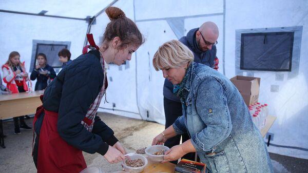 Волонтер раздает питание в полевом лагере