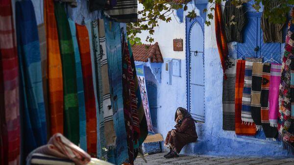 Женщина сидит на ступенях своего дома на одной из улиц города Шифшавен