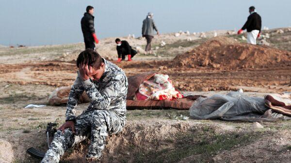 Иракский полицейский на месте массового захоронения в районе, который находился под контролем террористической группировки ИГ*