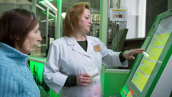Сотрудница поликлиники помогает пациентке оформить талон на прием к врачу. Архивное фото