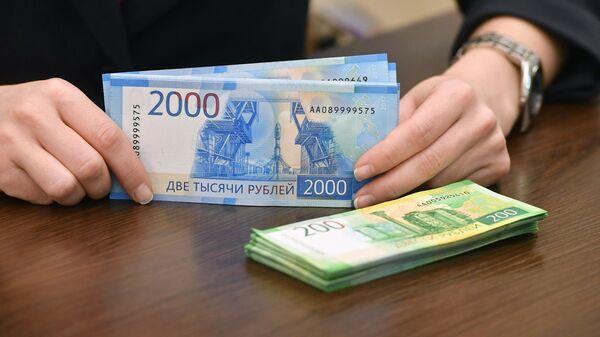 Сотрудница банка проводит денежные операции
