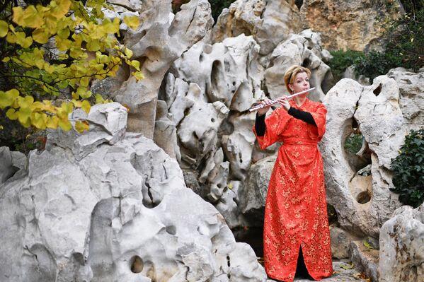 Артистка играет на флейте на открытии Японского сада на территории парка Айвазовское