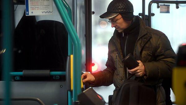 Пассажир оплачивает проезд в автобусе