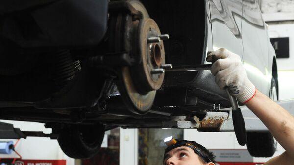 Сотрудник проводит техническое обслуживание автомобиля