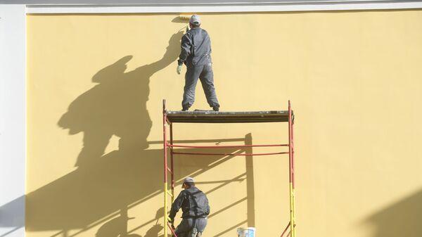 Рабочие красят фасад здания на одной из улиц Москвы