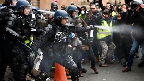Полиция использует перцовый баллончик против протестующих в желтых жилетах возле Оперы Гарнье в Париже, Франция