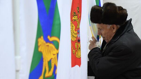 Мужчина голосует на повторных выборах губернатора Приморского края на избирательном участке во Владивостоке. 16 декабря 2018