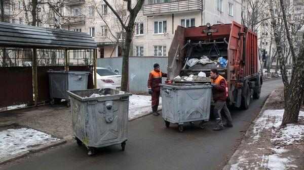 Сотрудники коммунальных служб выгружают мусор из контейнеров в мусоровоз