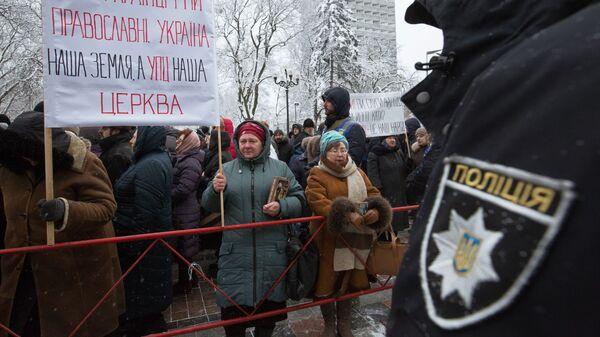 Верующие, протестующие против лишения канонической Украинской православной церкви ее названия, у здания Верховной рады Украины в Киеве