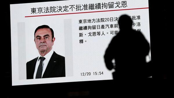 Новости о бывшем главе концерна Nissan Карлосе Гоне на телеэкране в Токио, Япония