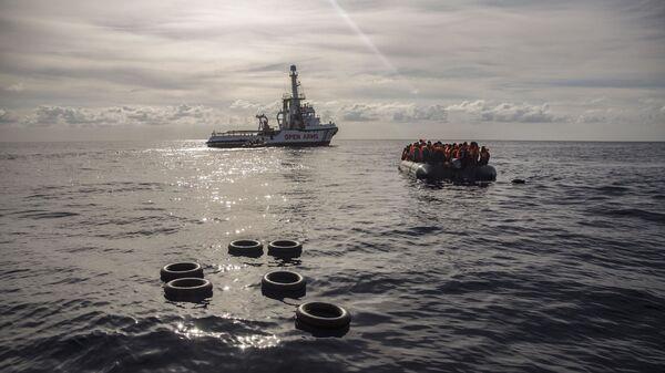 Лодка со спасенными мигрантами направляется к судну Open Arms в Средиземном море