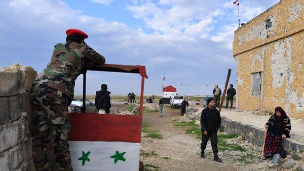 Военнослужащие и сирийские беженцы на территории гуманитарного коридора Абу-Духур в окрестностях провинции Идлиб