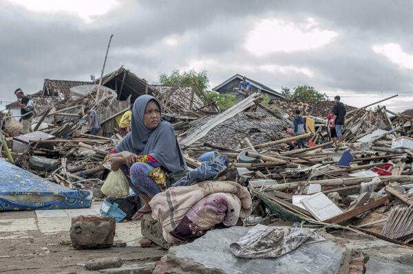 Местная жительница у своего дома, разрушенного цунами, в Сумуре, Индонезия. 24 декабря 2018