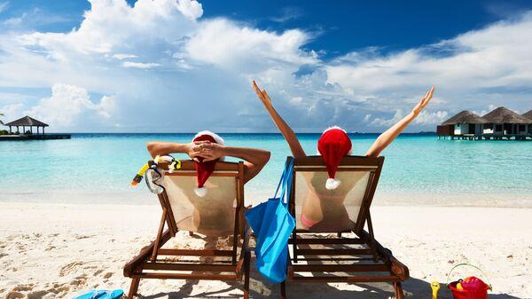 Пара в колпаках Санта Клауса на пляже на Мальдивах