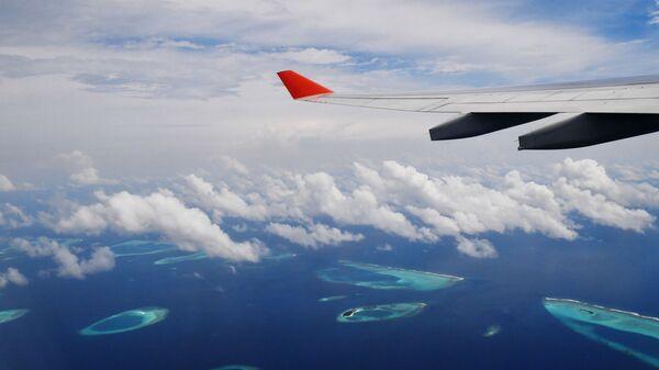 Самолет летит над Мальдивскими островами
